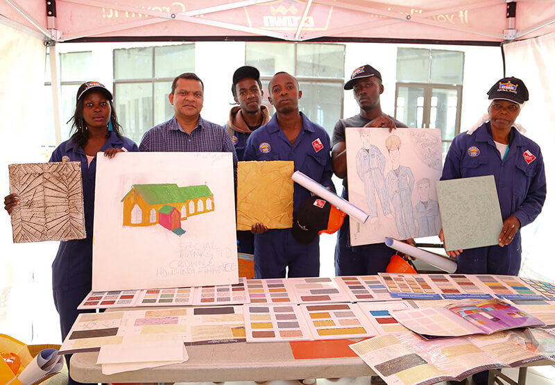 Crown Paints Group Marketing Manager, Nilesh Gosavi poses with the Housing Finance Graduates while displaying their designs.