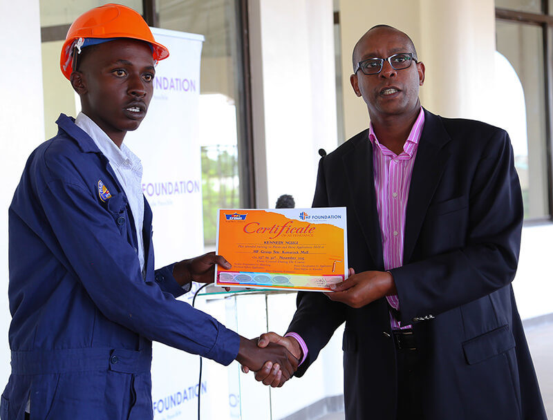 Housing Finance Group Managing Director, Frank Ireri presents a certificate to one the students during the Housing Finance Graduation Ceremony.