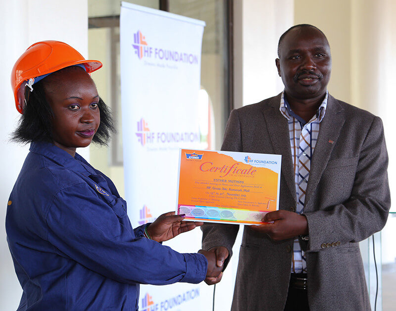 Director General TVETA, Dr. Kipkirui Langat presents a certificate to one the students during the Housing Finance Graduation Ceremony.
