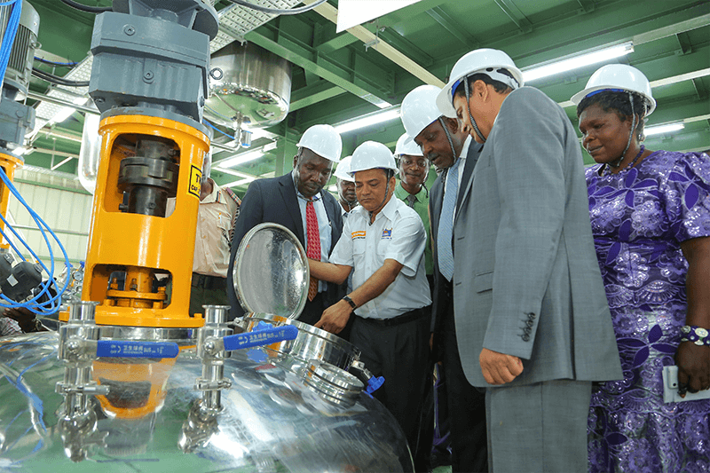 Crown Paints Kisumu- Factory Head, Shailesh Patel shows His Excellency the Governor of Kisumu, Hon Jack Raguma (second right) and the Crown Paints CEO, Rakesh Rao how some of the Paint machines functions.