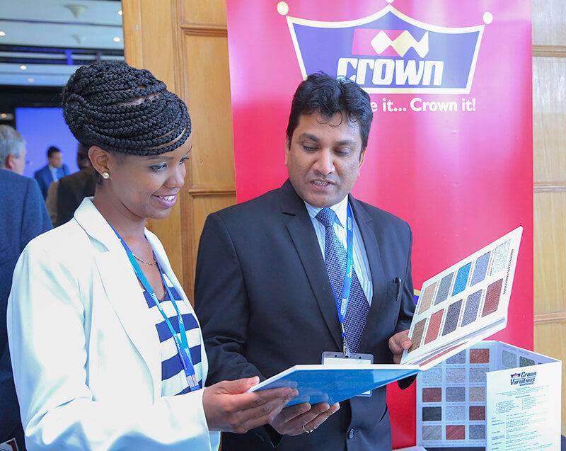Crown Paints, Head of Sales, Rakesh Ranjan (right) and Kenya Private Developers Association- CEO, Elizabeth Mwangi Oluoch go through different colour samples of paints available at Crown Paints.