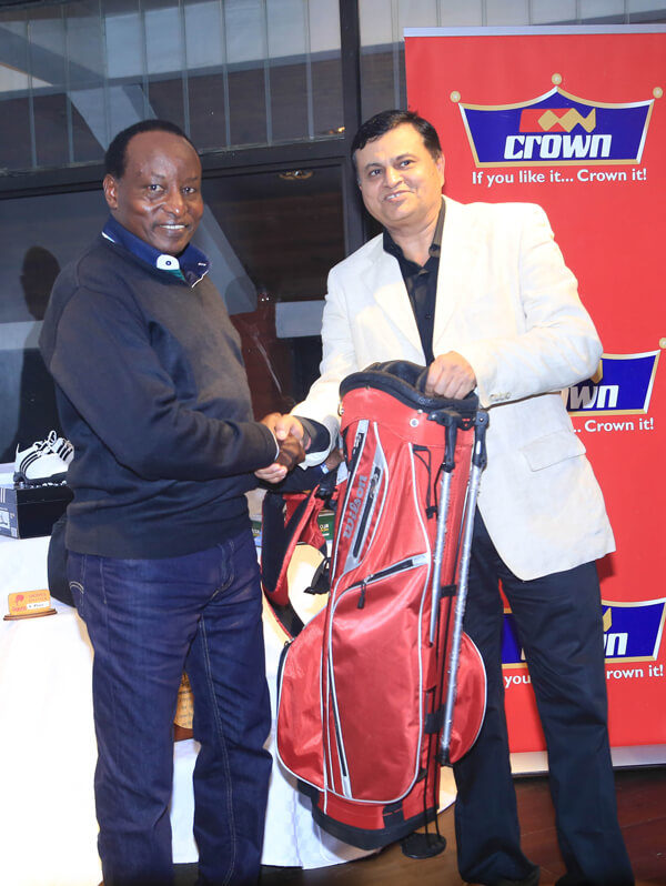 Crown Piants CEO Rakesh Rao presents the winners prize to Dave Mwangi after he emerged the winner during the Crown Paints Golf Day at Sigona Golf Club.