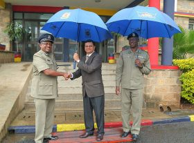 Crown Paints CEO, Rakesh Rao (centre), Japhet N Koome (left), MBS HSC Nairobi County Commander, and Nairobi County Commisioner of Police- Logistics, Aineah O Kaleb test two of the 665 umbrellas donated to Nairobi Traffic Police. This was out outside the Commander's office in Nairobi.